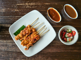 Thai food, grilled pork Satay with peanut sauce and pickles