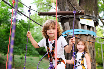 boy and a girl pass an obstacle course in a rope park