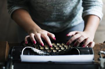 Woman typing vintage typewriter on wooden table