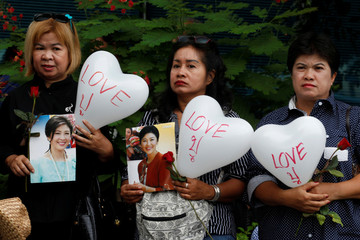 Supporters of ousted former Thai prime minister Yingluck Shinawatra holds a balloon with a sign of nickname and picture of Yingluck, while waiting for her arrival at the Supreme Court in Bangkok
