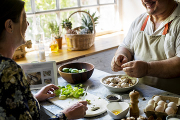 Closeup of people preparing vegetable to be cooked in the kitchen