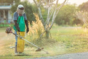 Man mowing cutting grass in his garden yard