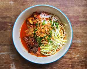 Northern Thai dish made from fermented rice noodles served with pork or chicken blood tofu in a sauce made with pork broth and tomato, crushed fried dry chilies, and dried red kapok flowers.