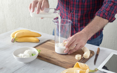 Man cooking healthy milkshake with banana and ice cream