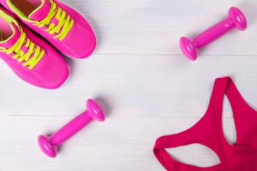 Women's sportswear, with pink dumbbells, on a light wooden floor