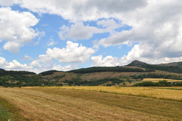 Beautiful field under a mountain and dramatic cloudy sky. Mountain summer landscape.