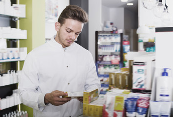 Glad man pharmacist standing among shelves