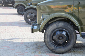 Photo of the cabins of three military off-road vehicles from the times of the Soviet Union. Side view of military cars from the front wheel