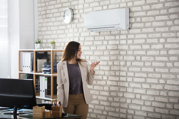 Businesswoman Using Remote Control Of Air Conditioner Wall mural