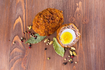 Scotch egg with spices on a wooden background
