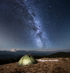 Night camping. Illuminated tourist tent under beautiful night sky full of stars and milky way. On the background snow-covered mountains and forests