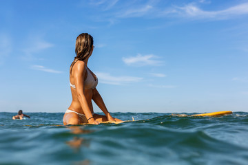 Two beautiful fit surfing girl in sexy bikini on surf surfboard board on sunrise or sunset in the ocean. Woman look how her friend swim in open sea. Modern active sport lifestyle and summer vacation.