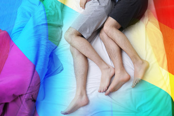 Legs of gay couple lying in bed