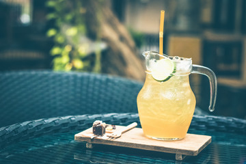 Honey and lemon iced tea with tiny dressert on the table. Healthy drink concept.