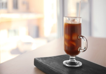 Glass cup of cold brew coffee and straw on light blurred background