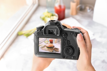 Woman taking photo of fast food with professional camera