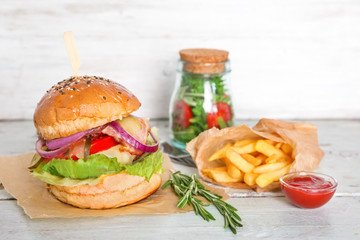 Composition with tasty homemade burger, french fries and bowl of ketchup on wooden table