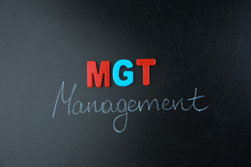 Abbreviation and text written on blackboard. Management concept