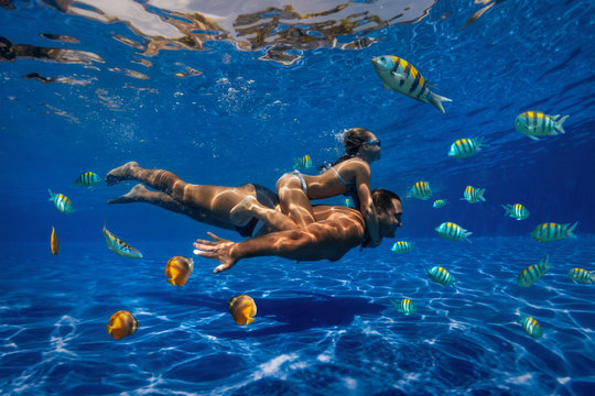 underwater image of a man and a girl