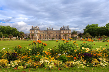 Jardin du Luxembourg with the Palace and statue. Few flowers are in front and blue sky behind.