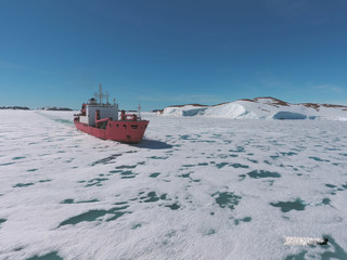 Cargo ship arrives in port for unloading on an ice floe. Antarctic.