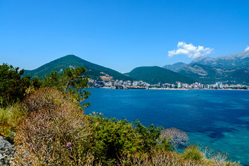 The beach along the coastline in Montenegro on the background of the mountains. View from the Adriatic Sea.