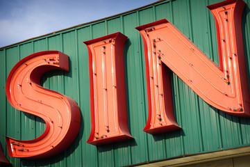 aged and worn neon sin sign