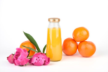 Orange fresh juice in bottles. Fruit and vegetable soft drink in a glass bottles isolated on white background. Pink flowers peonies