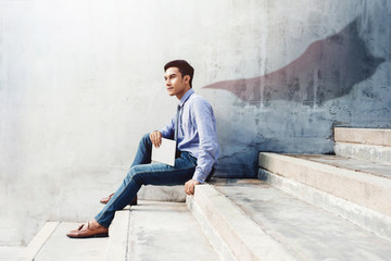 Power, Success and Leadership in Business concept, Young man sitting on office Outdoor Stair and looking forward with superhero blanket shadow shade on the wall, Side view