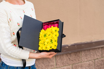 woman received a black gift box with sunflowers and bright French sweet pink macaroons outdoors. Celebrating holidays and happiness concept