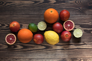 Sicilian Blood oranges, oranges, lemons and limes fruits over old dark wooden background. Top view. Toned.