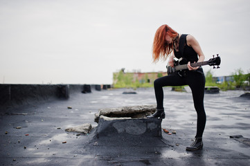 Red haired punk girl wear on black with bass guitar at the roof.