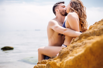 Sexy couple at sea,slim body,long hair,swimwear,swimsuit,beautiful tan,summer holidays concept,make up,bearded man