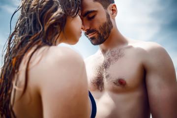Sexy couple at sea,slim body,long hair,swimwear,swimsuit,beautiful tan,summer holidays concept,make up,bearded man