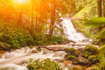 Fotobehang Bossen Huai Sai Lueang Waterfall with lens flare