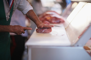 Butcher on the agricultural market prepares for sale beef fillet