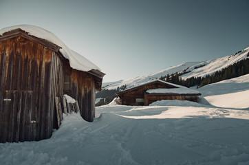 verschneite Hütten bei Saalbach-Hinterglemm in den Alpen bei Sonnenuntergang Wall mural