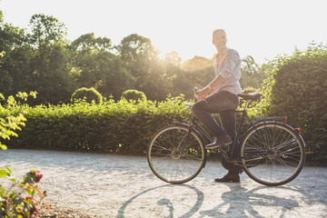 Man with bicycle in a park at sunrise