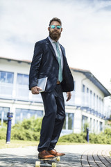 Portrait of businessman with sunglasses and tablet standing on skateboard