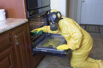 Woman in Haz Mat suit cleaning oven
