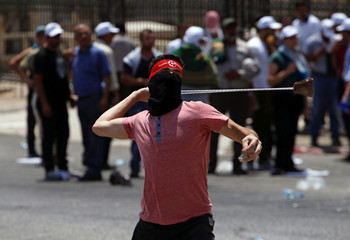 A Palestinian protester uses a sling to hurl stones towards Israeli troops during clashes in the West Bank city of Bethlehem