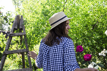 Girl in a blue checkered dress and a hat of a canoe in the country house among fruit trees