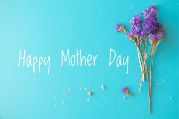 Write word happy mother's day on blue background with purple flowers.