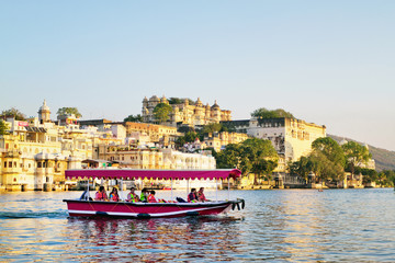 UDAIPUR, RAJASTHAN, INDIA - DECEMBER 8, 2011: Tourists on the boat taking Udaipur Lake Pichola sunset boat ride with City Palace on background