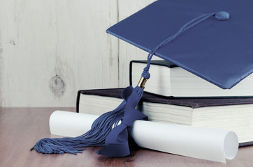 A blue graduation cap resting on two books with a diploma tied with blue ribbon on a wooden background. Copy space. White vignette added