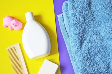 Baby bath products/ White shampoo bottle, soap, pink rubber toy hippo, blue cotton towel on a yellow and purple background. Flat lay photography with bathroom items