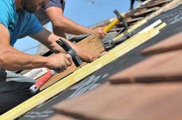 couvreurs clouant des lattes pour rénovation toiture
