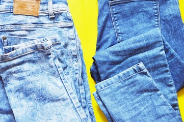 Blue jeans/ Blue denim jeans on a bright yellow background. Trendy women's clothing, mockup for design online store. Flat lay, top view photography. Shopping concept