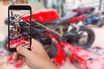 Close up hand  holding smartphone and take photo of motorbike accident