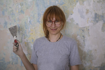 Home renovation - happy red hair woman with scraper near wall glues Wallpaper